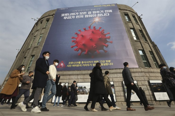 People wearing face masks walk under a banner emphasizing an enhanced social distancing campaign in front of Seoul City Hall in Seoul, Wednesday, Nov. 25, 2020. AP
