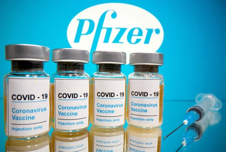 Coronavirus vaccine and a medical syringe are seen in front of a displayed Pfizer logo in this illustration taken October 31, 2020. /REUTERS