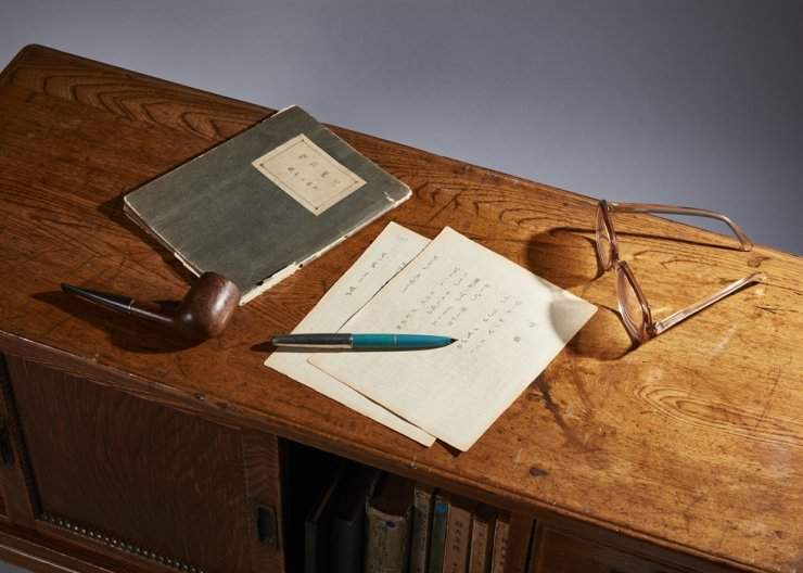 Cho's handwritten manuscripts, smoking pipe, fountain pen and glasses displayed on a stationery chest at the exhibition. / Courtesy of Korea University Museum