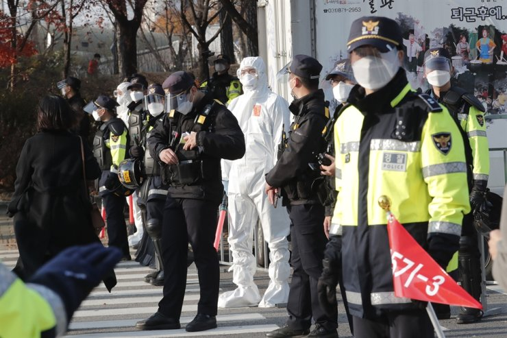 Police officers wearing face masks and shields to help protect against the spread of the coronavirus stand guard in Seoul, Saturday, Nov. 14, 2020. AP