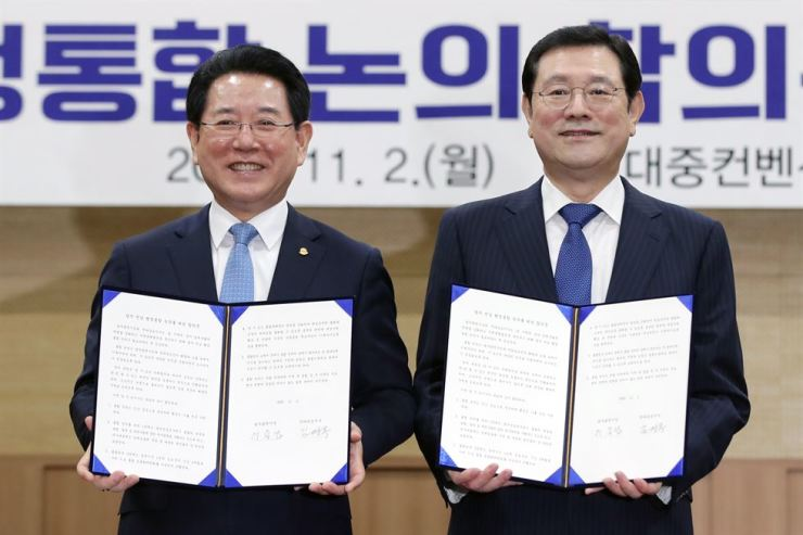 Gwangju Mayor Lee Yong-sup, right, and South Jeolla Governor Kim Young-rok hold an agreement for administrative integration during a ceremony in Gwangju, Nov. 2. Yonhap