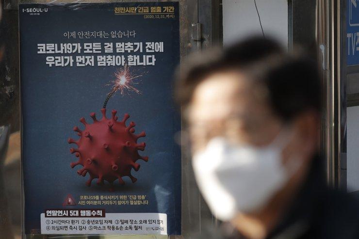 A man wearing face mask as a precaution against the coronavirus walks near a poster emphasizing an enhanced social distancing campaign in Seoul, Saturday, Dec. 12, 2020. AP