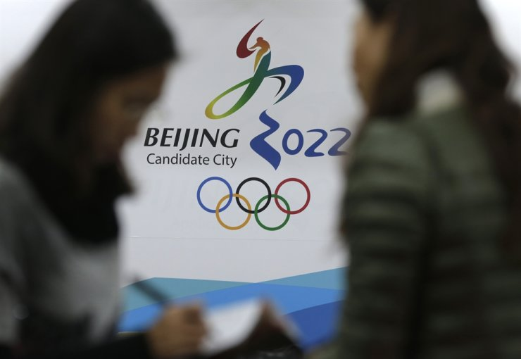 In this Nov. 4, 2014, file photo, journalists chat near the Beijing's bid for the 2022 Winter Olympics logo after attending a media briefing at the Beijing Olympics Headquarters in Beijing. AP