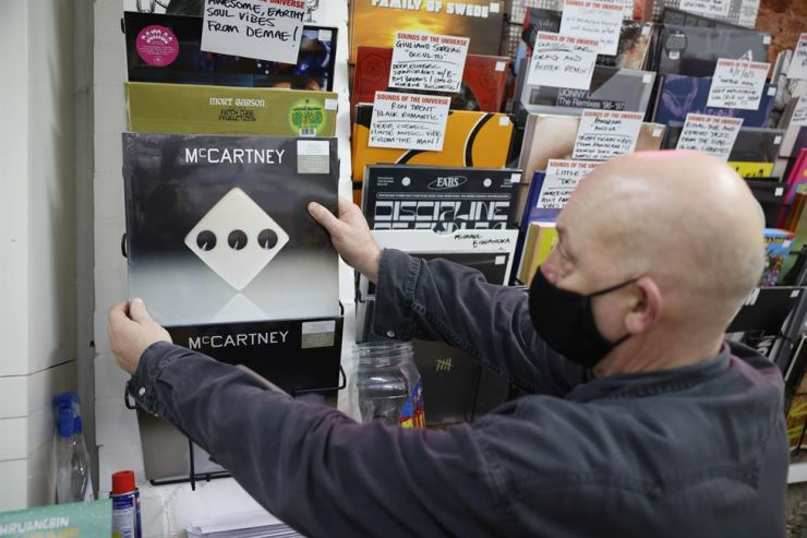 Karl Shale poses with a copy of the newly released album McCartney III by British musician Paul McCartney in the Sounds of Universe record store in London on December 18, 2020. AFP-Yonhap