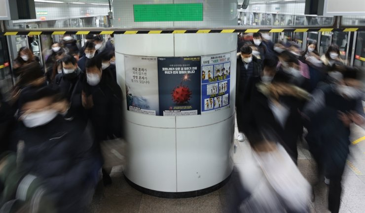 Morning commuters crowd a Gwanghwamun subway station platform in Seoul's Jongno District, Thursday. The posters on a pillar urge to wear facial masks and do cautionary measures to minimize the COVID-19 risks. Yonhap