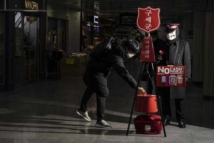 A pedestrian makes a donation at the Salvation Army's red kettle located in Seocho Subway Station in Seoul, Monday. The charity group's iconic campaign will continue until the end of this year. / Korea Times photo by Choi Won-suk