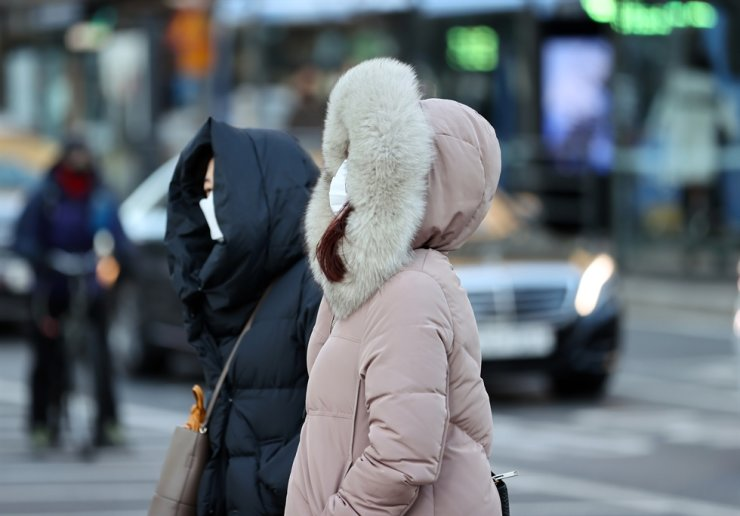 Women wearing masks and coats walk in the street in central Seoul, Tuesday. Yonhap