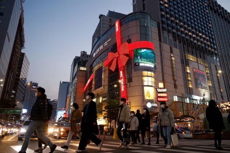 People walk on a zebra crossing in front of a department store in Christmas season themed decorations amid the COVID-19 pandemic in Seoul, Nov. 26, 2020. Reuters