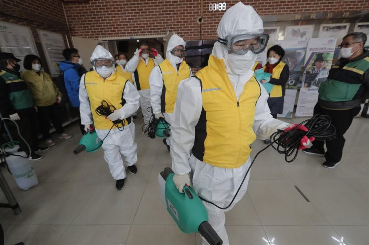 Health officials arrive to disinfect classrooms before the college entrance exams at a high school in Seoul, Tuesday, Dec. 1, 2020. AP