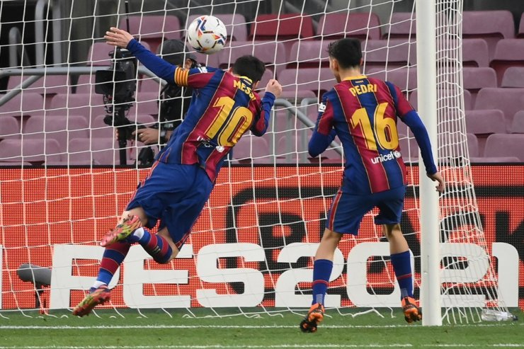 Barcelona's Argentinian forward Lionel Messi (L) scores a goal during the Spanish league football match between FC Barcelona and Valencia CF at the Camp Nou stadium in Barcelona on December 19, 2020. AFP-Yonhap