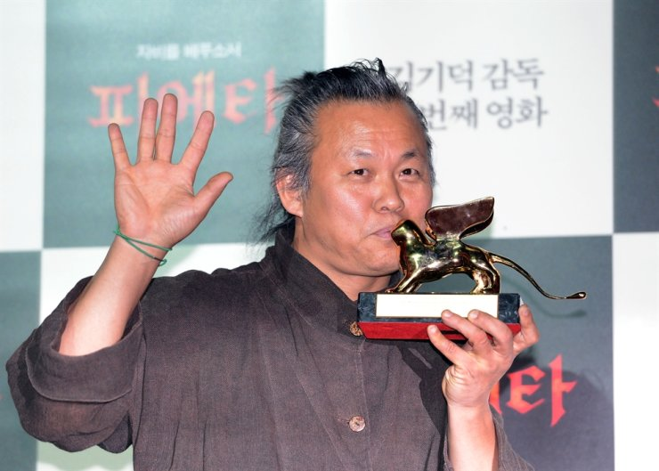 Kim Ki-duk kisses his golden lion award from the 69th Venice International Film Festival in 2012 he won with 'Pieta' at a press conference at Mega Box Dongdaemun in Seoul's Jung District in September 2012. Korea Times file