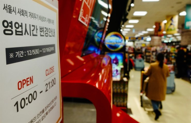 A notice is posted at a supermarket in Seoul, Sunday, announcing changes in its operating hours, as the Seoul Metropolitan Government forced stores, movie theaters and several other facilities to close after 9 p.m. for two weeks starting Saturday to help curb the spread of COVID-19. For its part, the central government announced a decision to raise its social distancing scheme to Level 2.5 in Seoul and its surrounding areas, starting Tuesday, amid the third wave of infections. / Yonhap
