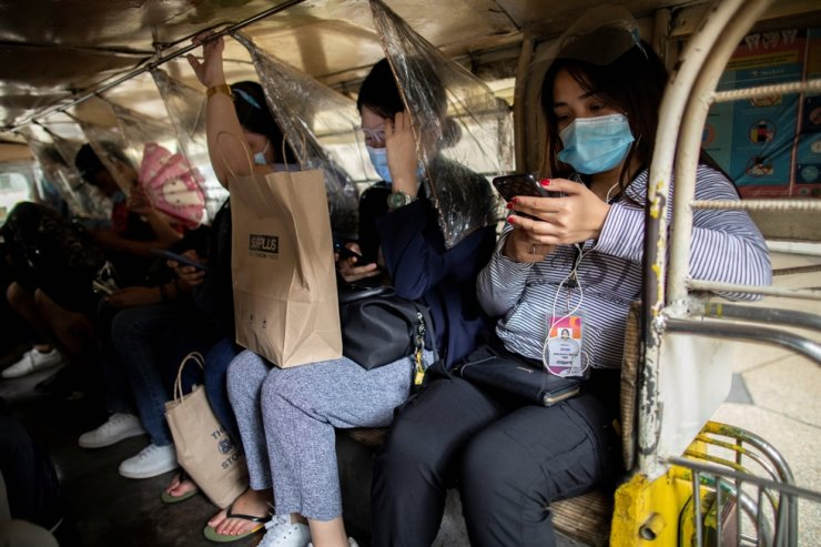 Passengers wearing masks and face shields for protection against the coronavirus disease (COVID-19) sit between plastic barriers inside a jeepney in Makati City, Metro Manila, Philippines, Jan. 27, 2021. Reuters