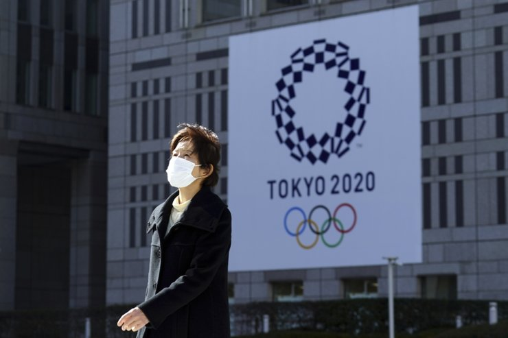 A woman wearing a protective mask to help curb the spread of the coronavirus walks near a banner of the Tokyo 2020 Olympics in Tokyo, Tuesday, Jan. 19, 2021. AP