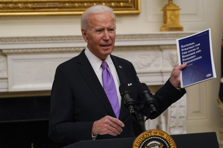 President Joe Biden holds a booklet as he speaks about the coronavirus in the State Dinning Room of the White House, Thursday, Jan. 21, 2021, in Washington. AP-Yonhap