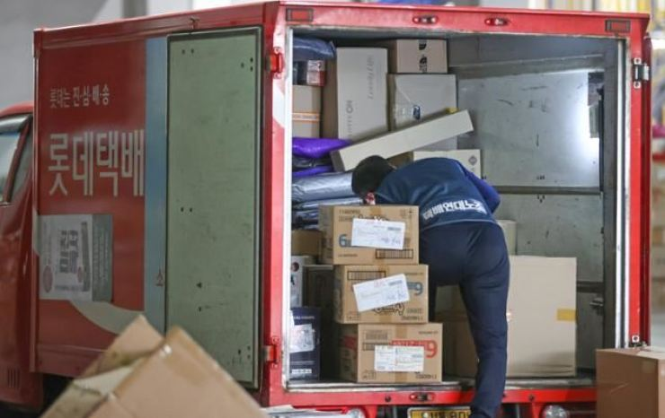 A delivery driver loads packages at a distribution center in Seoul, Nov. 10, 2020. / Korea Times file