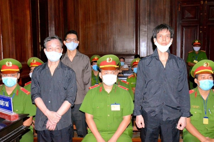 This picture taken and released by the Vietnam News Agency on Jan. 5, 2021, shows Vietnamese bloggers Pham Chi Dung (R), Nguyen Tuong Thuy (L) and Le Huu Minh Tuan (3rd L) during their trial at the courthouse in Ho Chi Minh city. Vietnam has jailed three independent bloggers on anti-state charges, one of their lawyers said, weeks ahead of the coummunist government's party congress. AFP