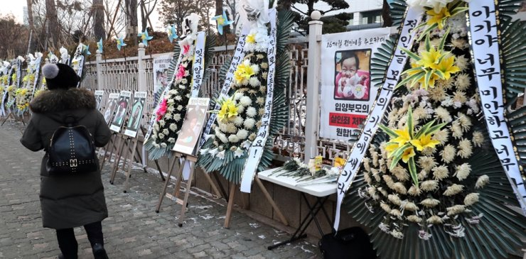Flowers and photos of Jung-in, a 16-month-old baby girl who died after being abused by her adoptive mother, are placed near the Seoul District Prosecutors' Office in southern Seoul, Tuesday. Yonhap