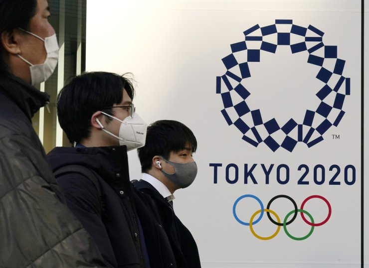 Pedestrians wearing protective masks walk past the emblem of Tokyo 2020 Olympic Games in Tokyo, Japan, 21 January 2021 (issued 22 January 2021). EPA