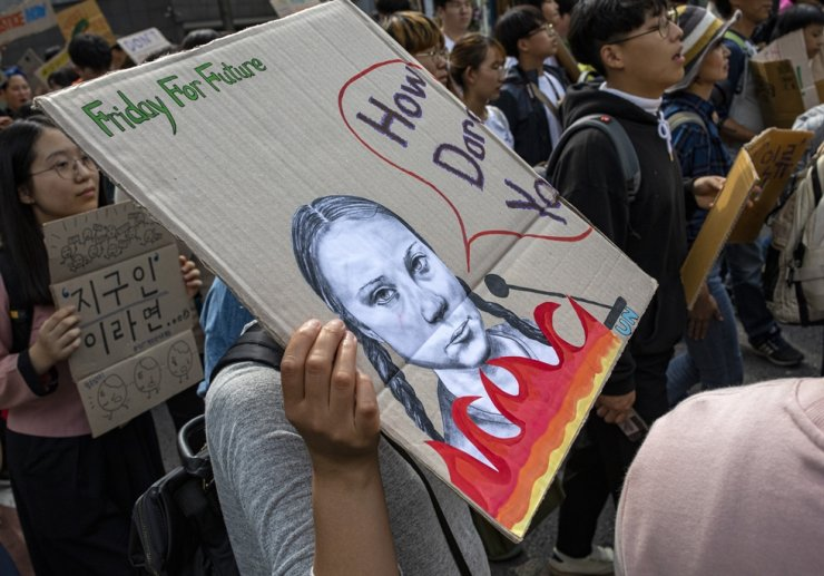 One of the students participating in the street demonstration on Sept. 27, 2019, hosted by Youths 4 Climate Action at Gwanghwamun Square, holds a piece of cardboard showing an illustration of Greta Thunberg. Korea Times photo by Shim Hyun-chul