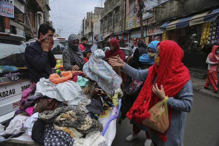 Indians, some of them, wearing face masks shop at a Sunday market in Jammu, India, Sunday, Jan.3, 2021. India authorized two COVID-19 vaccines that day, paving the way for a huge inoculation program to stem the coronavirus pandemic in the world's second most populous country. AP