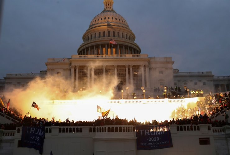 An explosion caused by a police munition is seen while supporters of U.S. President Donald Trump gather in front of the U.S. Capitol Building in Washington, U.S., Jan. 6, 2021. Reuters