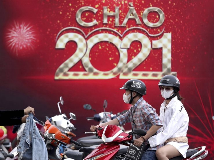 People wearing face masks ride a scooter in front of a banner welcoming New Year 2021 in Vung Tau city, Vietnam, Dec. 31, 2020. AP