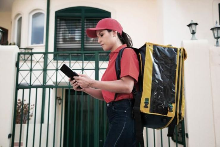 A deliverywoman looks at her device while on the move. / Korea time file