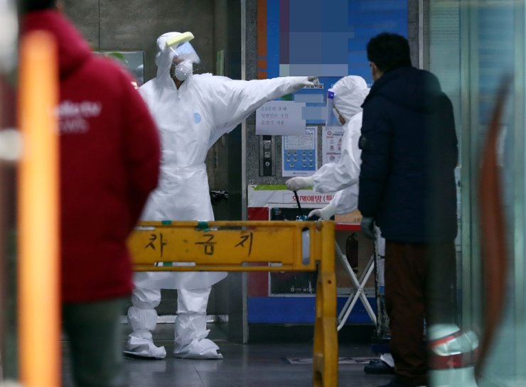 Quarantine officials in protective gear disinfect themselves at a nursing home in Incheon, Monday, following coronavirus infections there. Yonhap