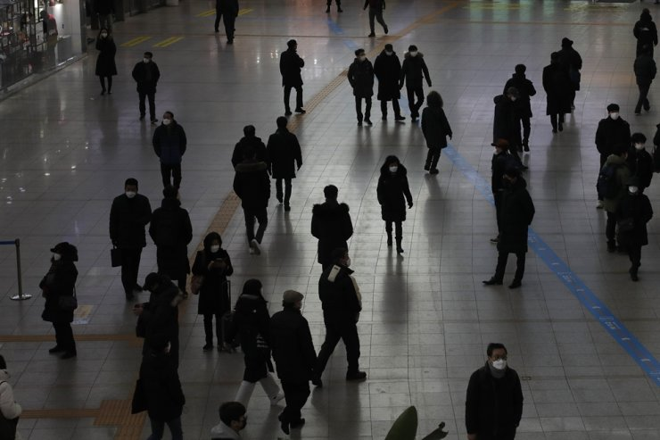 People wearing face masks as a precaution against the coronavirus walk at the Seoul Railway Station in Seoul, Monday, Jan. 11, 2021. AP