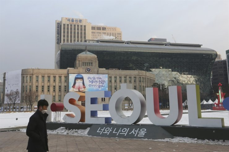 A man walks by the display of the capital city's logo near the Seoul City Hall in Seoul, Tuesday, Jan. 12, 2021. AP