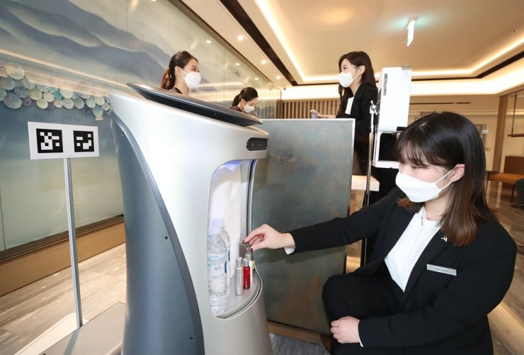 Hotel workers Marriott Hotel & Residence in the southeastern city of Daegu operate a KT AI-powered robot in this photo. / Courtesy of KT