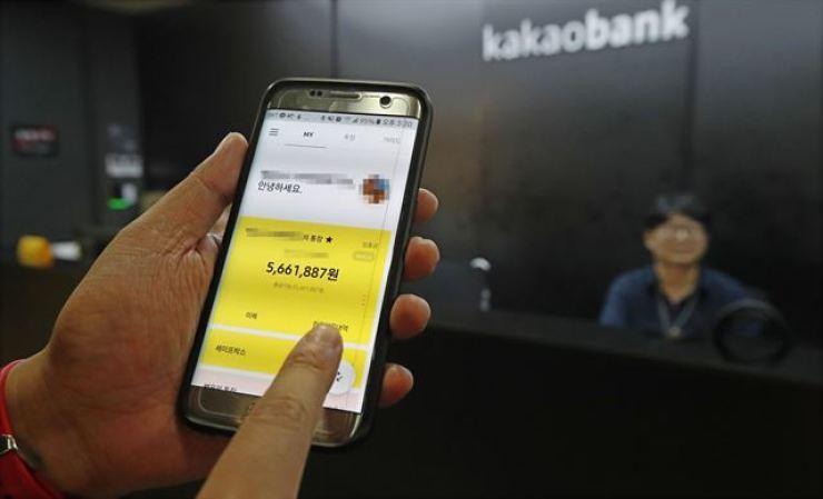 A smartphone user views Kakao Bank's mobile banking app. Korea Times file