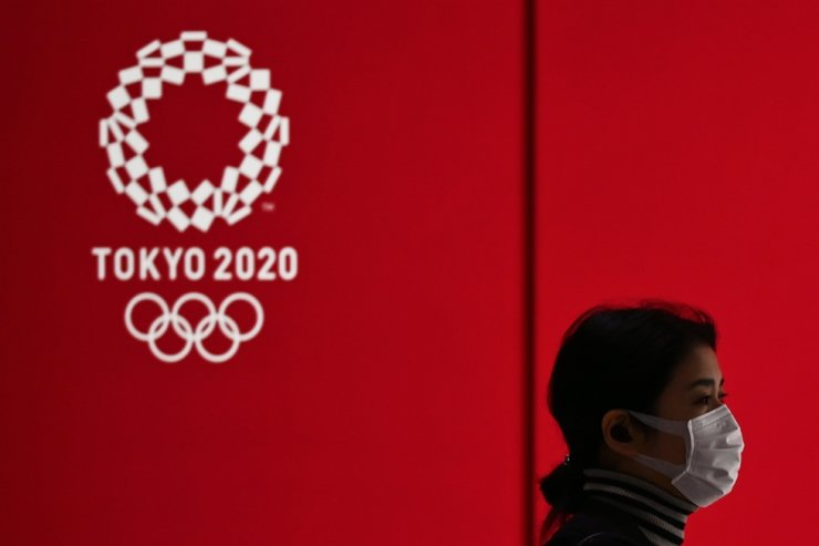 In this file photo taken on March 24, 2020, a woman in a face mask walks past a display showing the Tokyo 2020 Olympic Games logo in Tokyo. AFP
