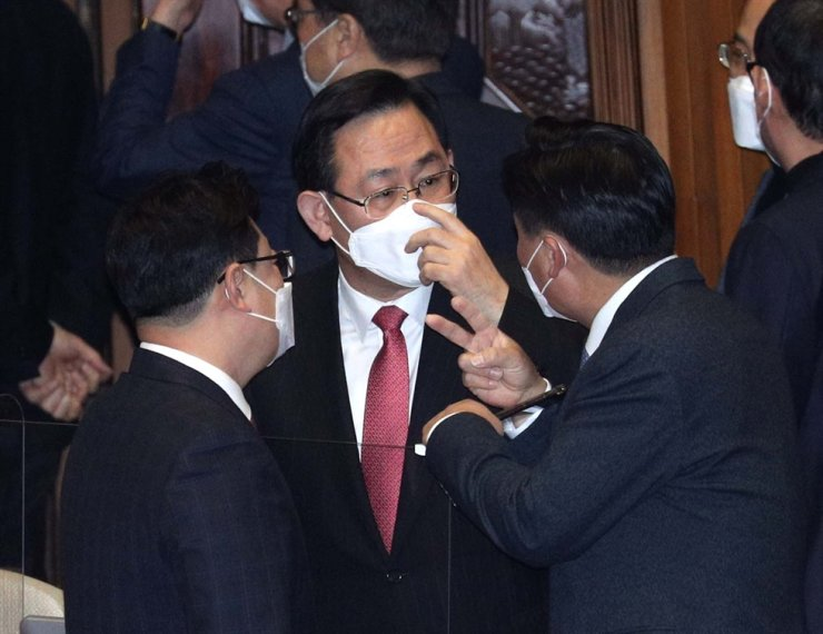 Rep. Joo Ho-young of the main opposition People Power Party, center, talks with Rep. Kim Young-jin with the ruling Democratic Party of Korea, right, during a plenary session at the National Assembly in Seoul, Jan. 8. Yonhap