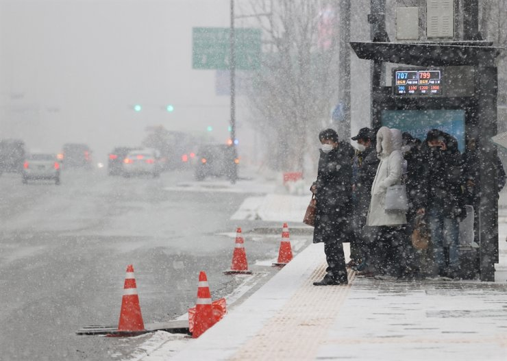 Residents wait at a bus station near Gwanghwamun Square in central Seoul, Tuesday, as heavy snow began to fall in the afternoon. Heavy snow alerts were issued for central regions of the Korean Peninsula including the capital, Incheon, Gyeonggi Province and South Chungcheong Province, with the Ministry of the Interior and Safety warning of ice forming on roads. / Yonhap