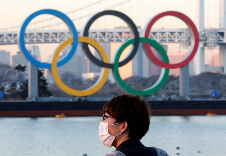 A man wears a protective mask amid the coronavirus (COVID-19) outbreak in front of the giant Olympic rings in Tokyo, Jan. 13, 2021. Reuters