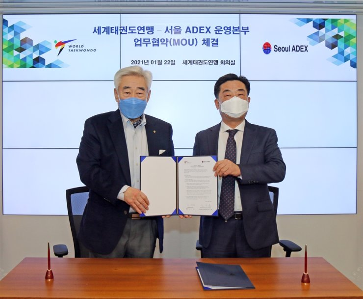 World Taekwondo President Choue Chung-won, left, and Seoul ADEX's executive director Jang Suk-chul signed a memorandum of understanding at WT's headquarters in Seoul's Jung District, Jan. 22, agreeing that WT's taekwondo demonstration team will perform during the opening ceremony of Seoul ADEX Air Show in October. Courtesy of World Taekwondo