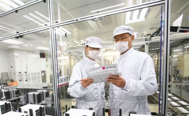 LG Chem researchers hold an electric vehicle battery module at the company's plant in North Chungcheong Province in this undated file photo. Courtesy of LG Chem