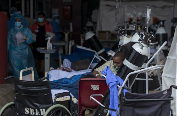 A patient wearing an oxygen mask is being treated in makeshift emergency units at Steve Biko Academic Hospital in Pretoria, South Africa, Monday, Jan. 11, 2021. AP