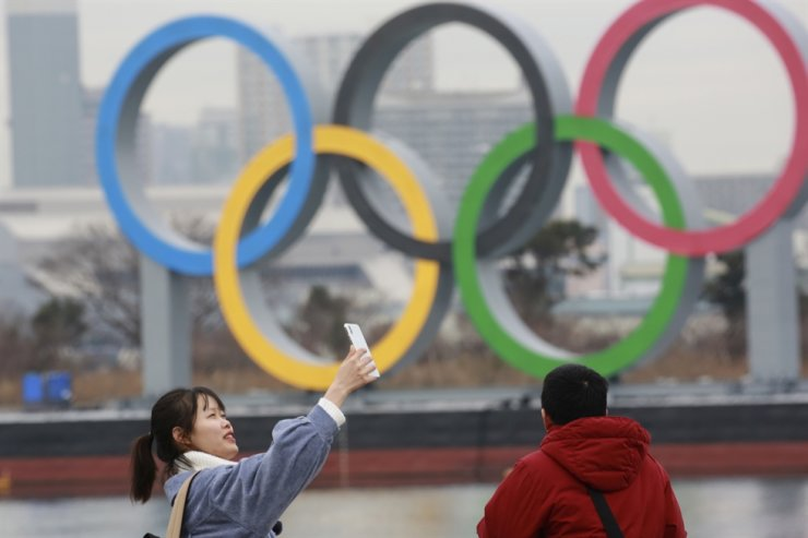 A woman poses for a selfie in front of Olympic rings at Odaiba waterfront in Tokyo, Tuesday, Jan. 26, 2021. The postponed Tokyo Games are scheduled to open on July 23. AP
