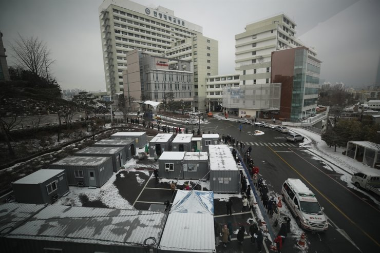 Visitors to Hanyang University Seoul Hospital in the city's Seongdong District queue up to an early COVID-19 testing center inside the campus where cluster infection cases of the disease were reported. Yonhap