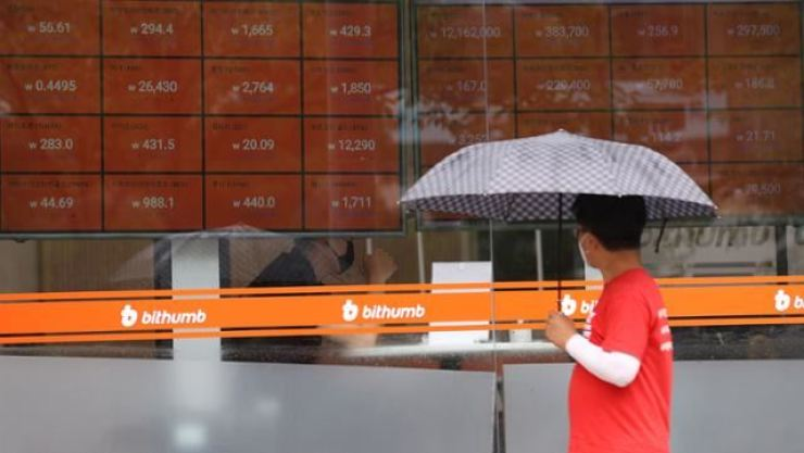 A pedestrian passes by the Bithumb Korea headquarters in Seoul in this file photo. / Yonhap