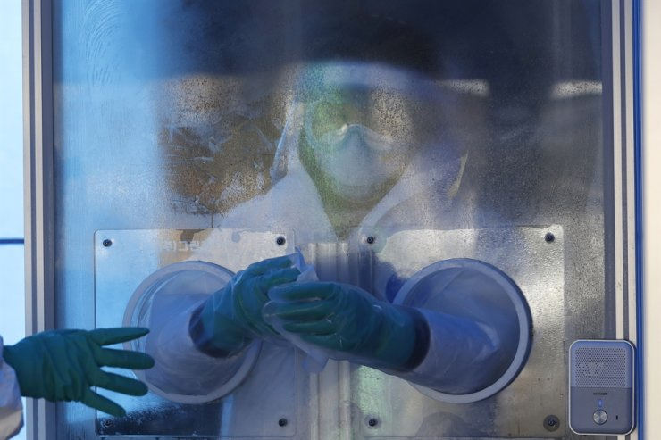 A medical worker wearing protective gear disinfects gloves in the sub-zero temperatures at a coronavirus testing site in Seoul, Feb. 16, 2021. AP