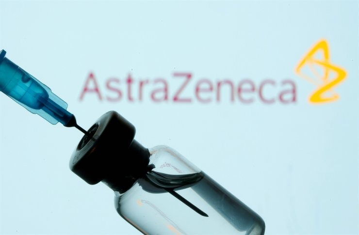 A vial and sryinge are seen in front of a displayed AstraZeneca logo in this illustration taken Jan. 11, 2021. Reuters