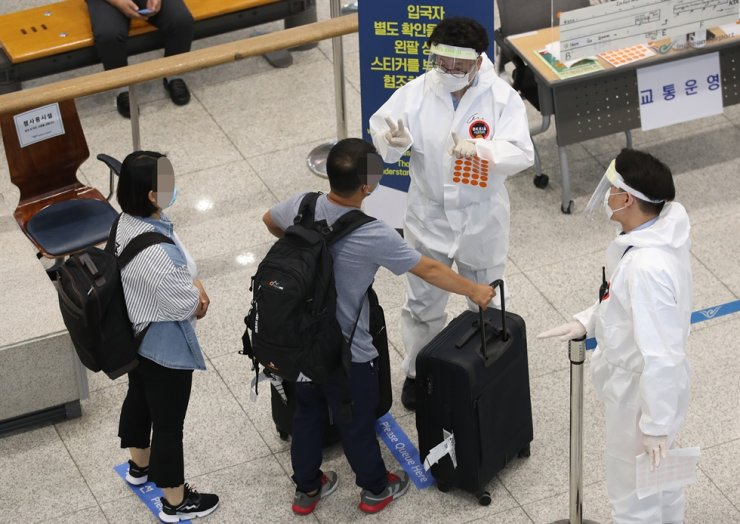 Quarantine officials guide foreign arrivals at Incheon International Airport Terminal 1 amid the prolonged COVID-19 pandemic in this July 12 file photo. / Yonhap
