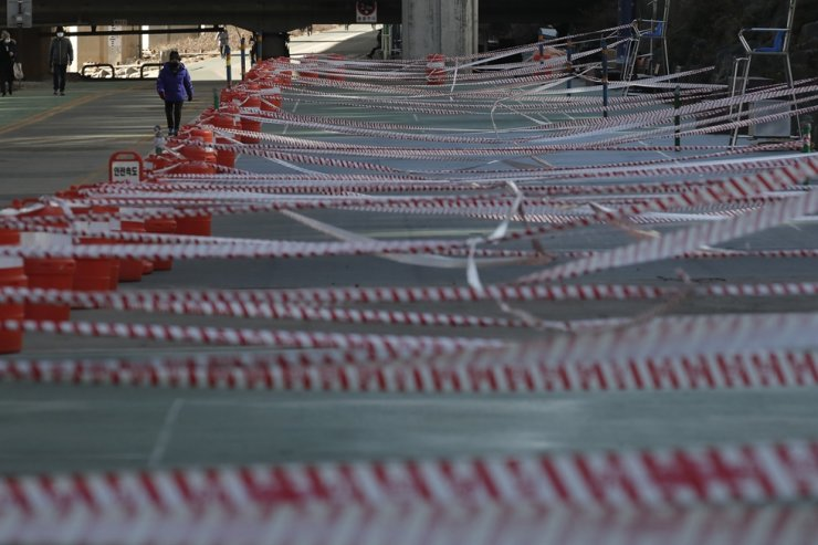 Visitors wearing face masks walk near a public sports facilities area in Seoul which is taped off for social distancing measures imposed as a precaution against the spread of COVID-19, Feb. 9. AP