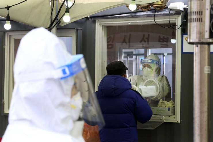 A medical worker in a booth takes a nasal sample from a man at a coronavirus testing site in Seoul, Monday, Feb. 15, 2021. AP