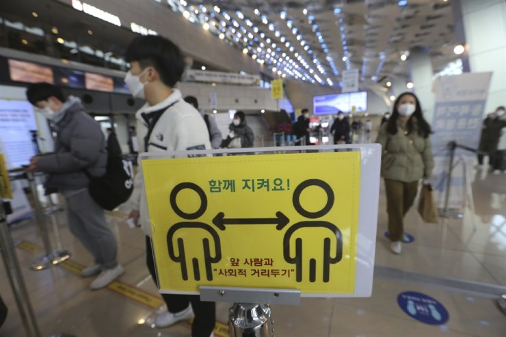 A social distancing sign is seen as passengers wait to board planes on the eve of the Lunar New Year holiday at the domestic flight terminal of Gimpo International Airport in Seoul, Feb. 11. AP