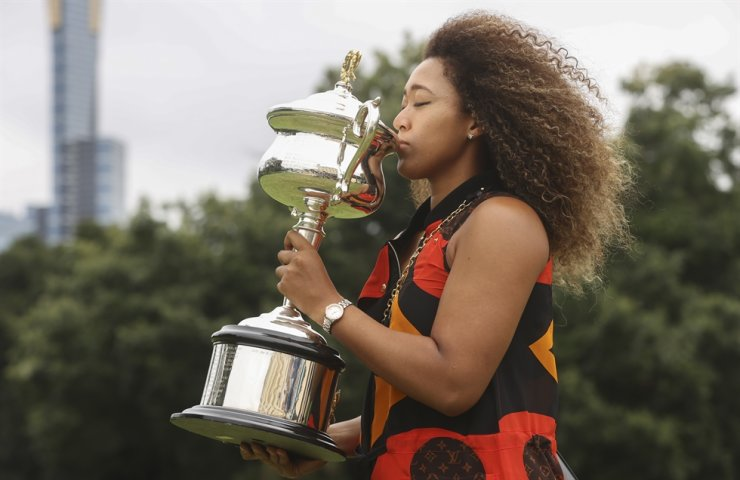 Japan's Naomi Osaka kisses the Daphne Akhurst Memorial Cup during a photo shoot at Government House the day after defeating Jennifer Brady in the women's singles final at the Australian Open tennis championship in Melbourne, Australia, Sunday, Feb. 21, 2021. AP